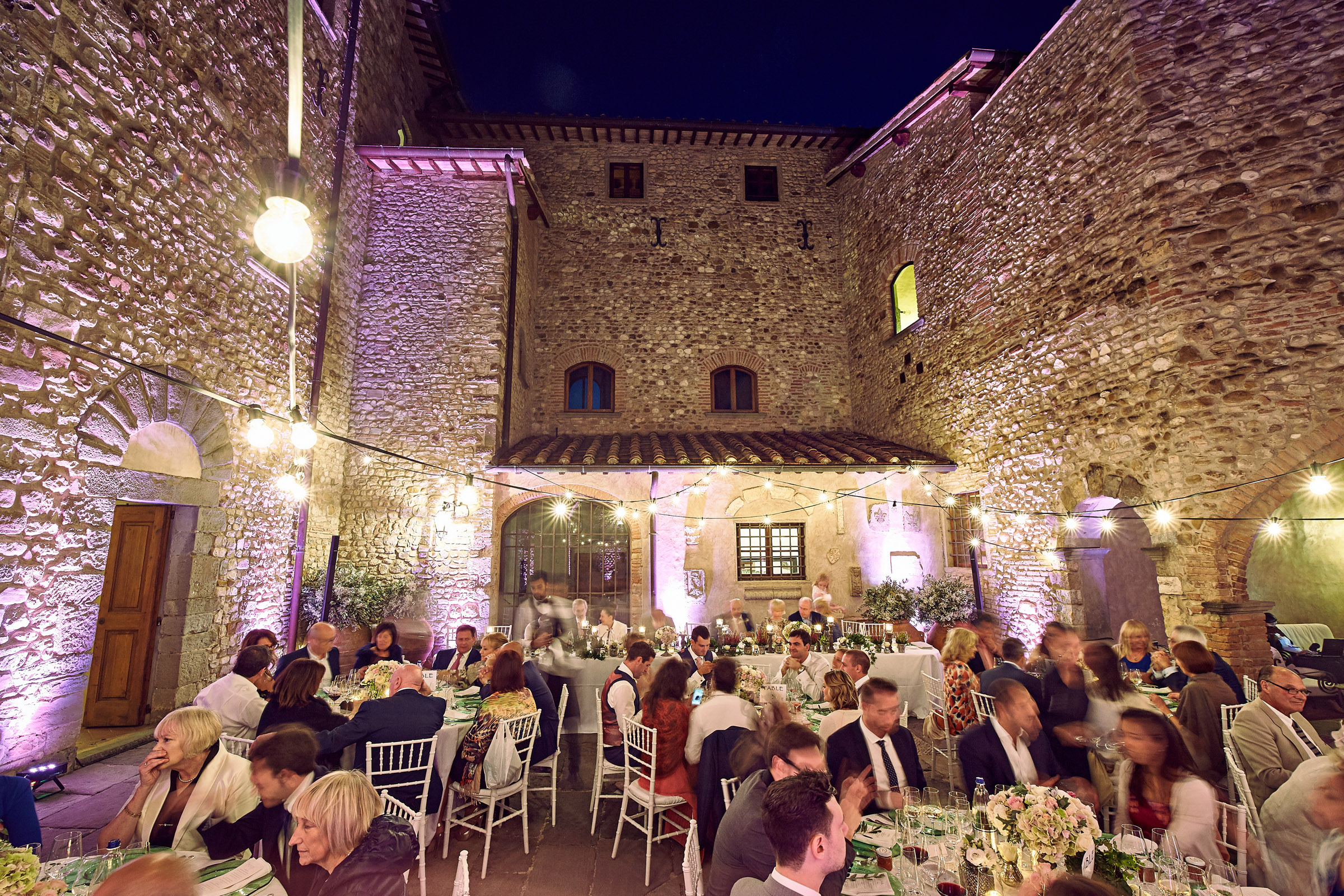 Castle courtyard illuminated with colored spots and string lights
