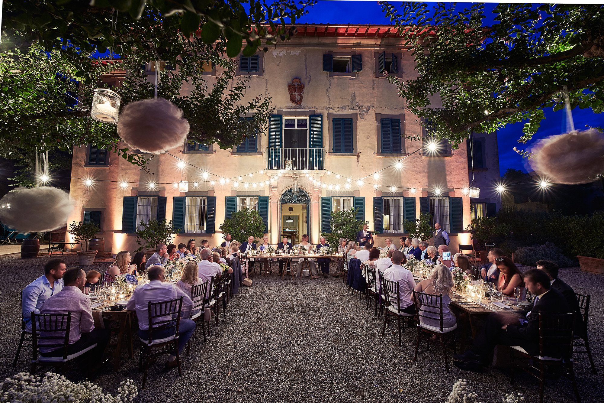 Wedding dinner in Tuscan villa illuminated with string lights