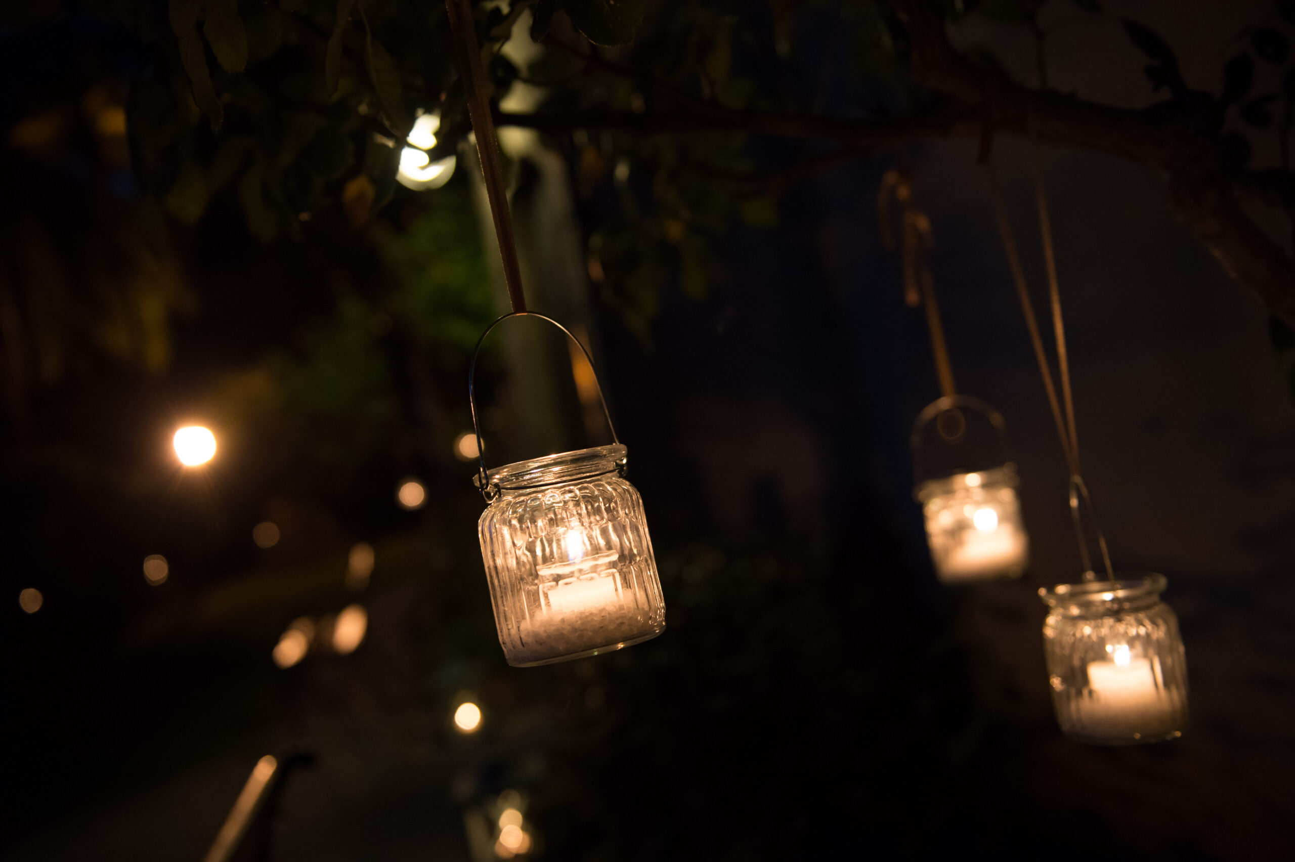 Hanging glass jars with candles from trees create a nice atmosphere for weddings in Tuscany