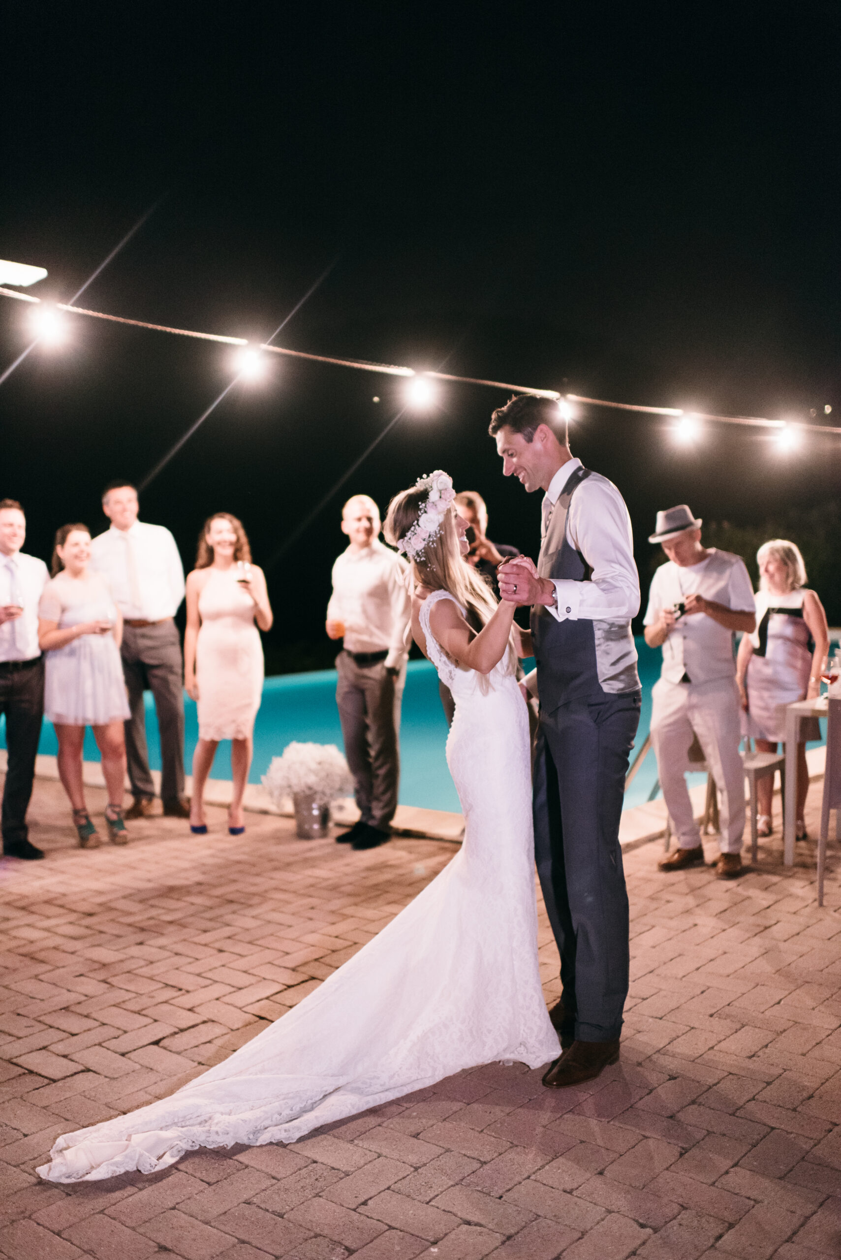 Wedding couple dancing by the pool side